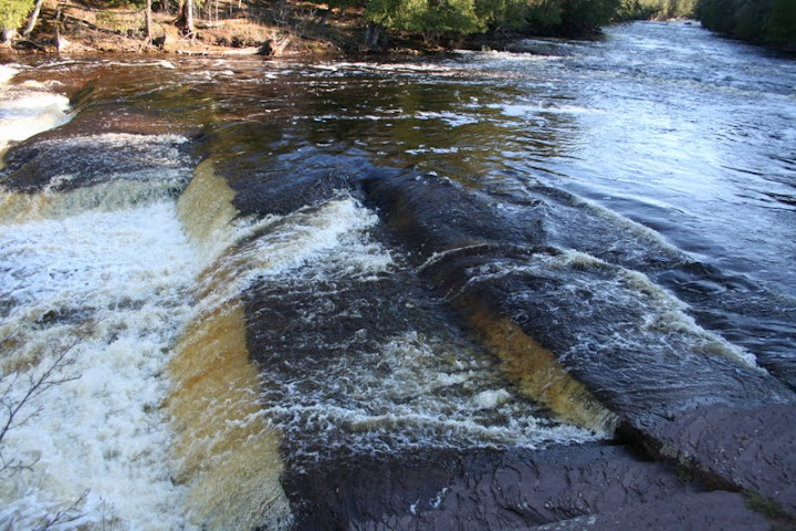 This is a view of one of the falls on the Presque Isle River. There are two falls that are channeled into two other rivers. The falls gives a clear view of the bedrock of the area. The falls also impaired the logging industry due to the inability to transport the logs over the falls without jamming.-Ashley Holloway