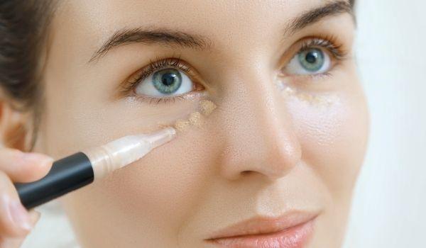 lady using eye concealer