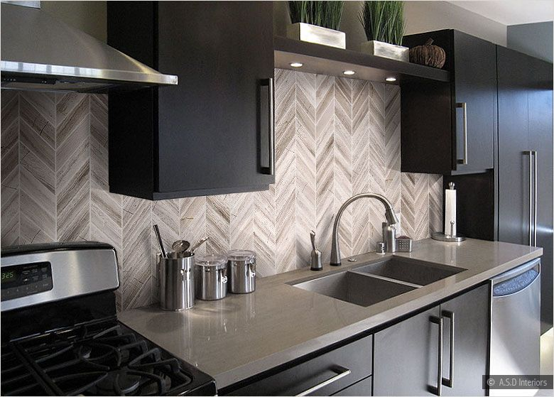 modern brown kitchen with espresso cabinets and neutral herringbone backsplash
