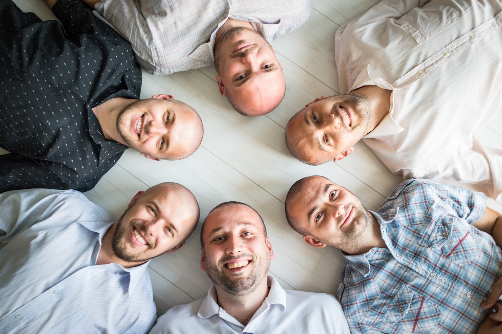 A group of men laying with their heads together in a circle on the floor
