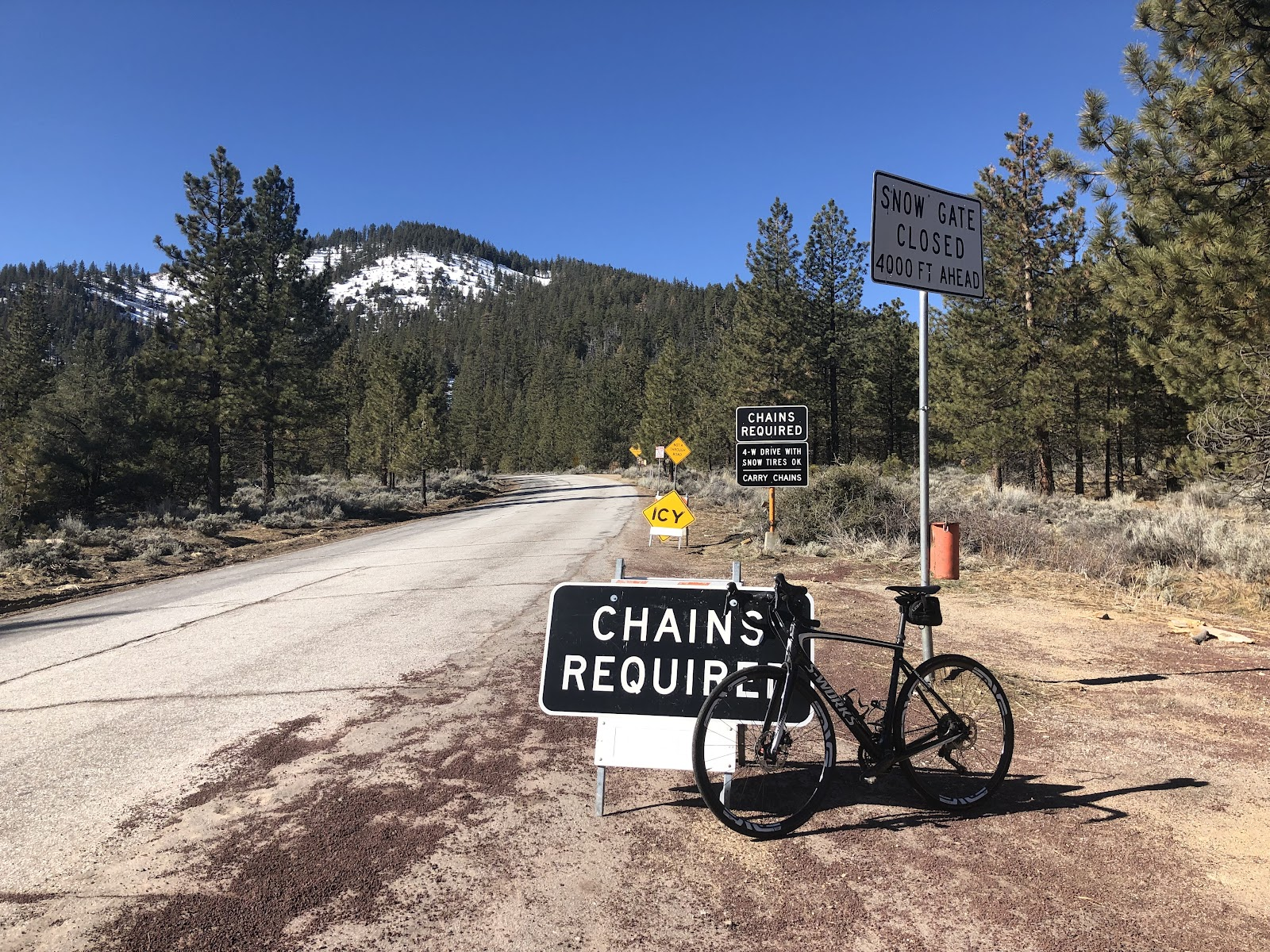 Climbing by bike Mt. Pinos - bike leaning against chains required sign, road, snow covered mountain