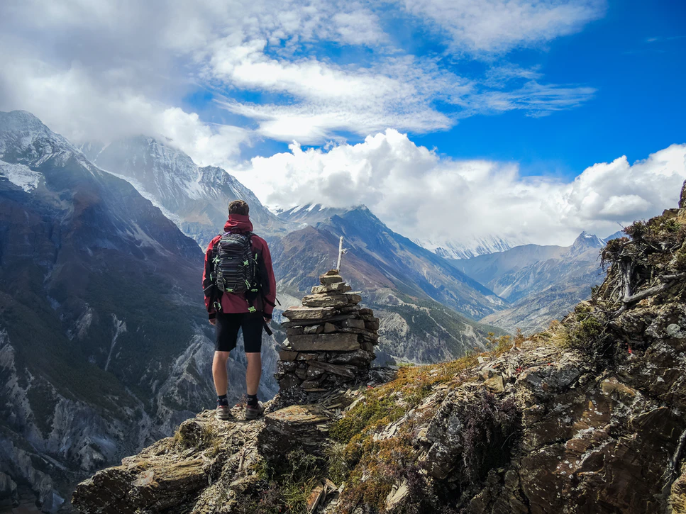 a man with a backpack on top of the mountain