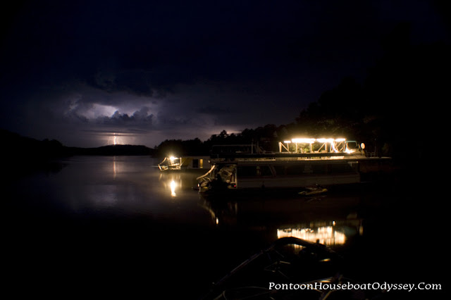 """Houseboats moored in a sheltered cove for the night as a summer storm rumbles and approaches in the distance."""""""
