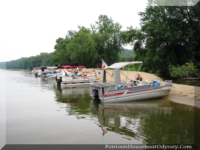 Several pontoon boats beached up on an sandbar for an afternoon of fun and sun.
