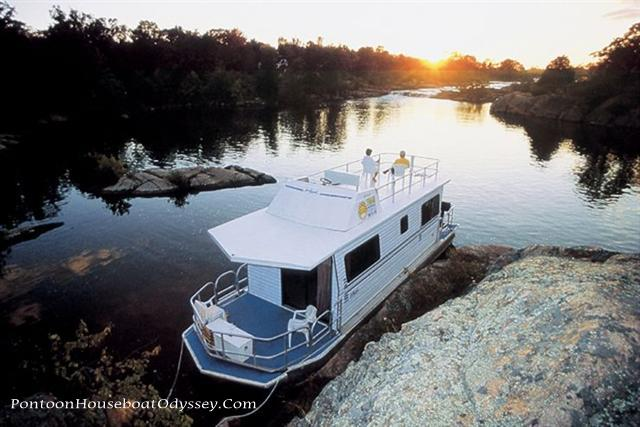 """House boaters viewing and enjoying the sunrise tied off in a peaceful rocky cove with reflections upon the water"