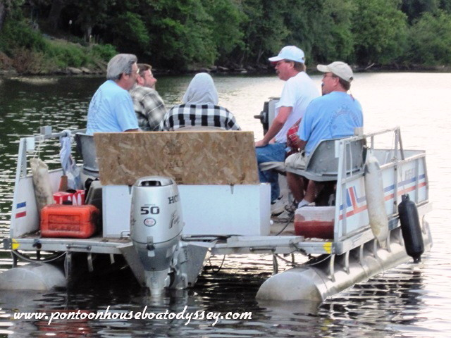 An old pontoon boat floating in the Muskingum River with its five occupants engaged in conversation.
