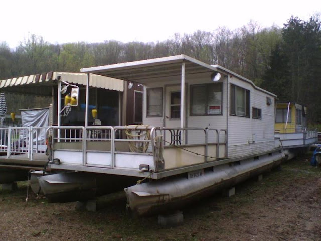 """Our pontoon houseboat as it appeared when we first purchased it or should I say bought it"