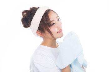 爽やかな朝にタオルを持って顔を洗う女性