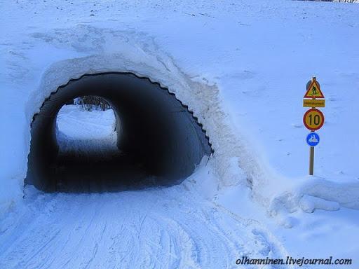 Дорожные знаки перед туннелем об ограничении скорости до 10 км для въезда мотосаней и лыжников