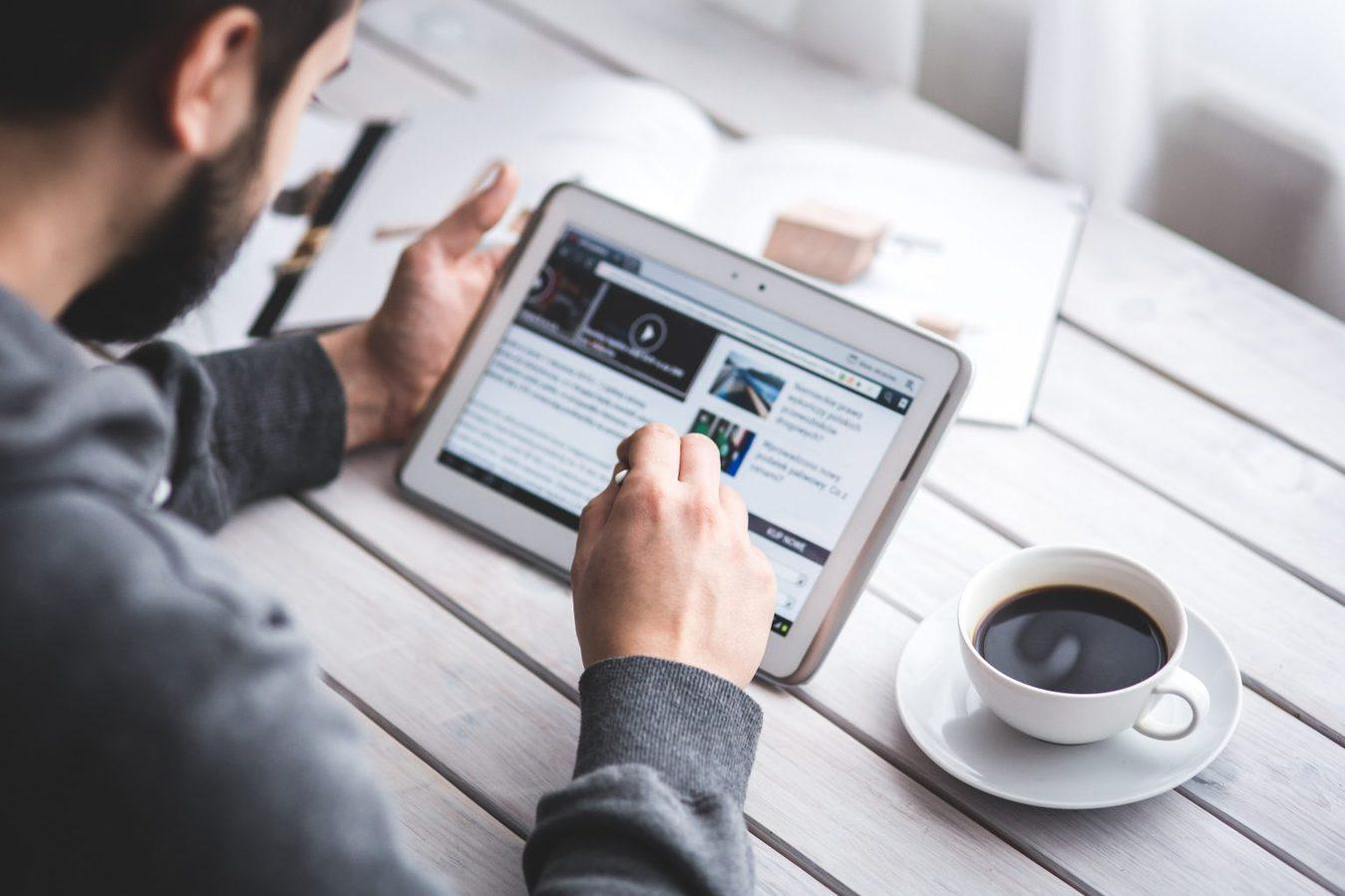 man with cup of coffee reading news on ipad