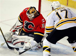 Mikka Kiprusoff making a save and Milan Lucic looking for a rebound