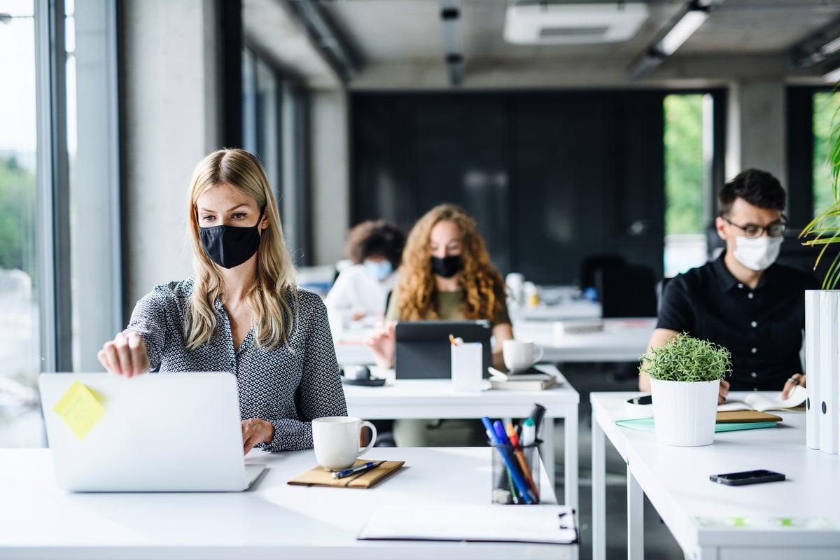 Três mulheres e um homem num escritório, com máscara e distanciamento social a trabalharem