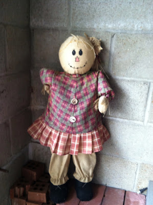 Scarecrow doll bricks cinder block wall photo