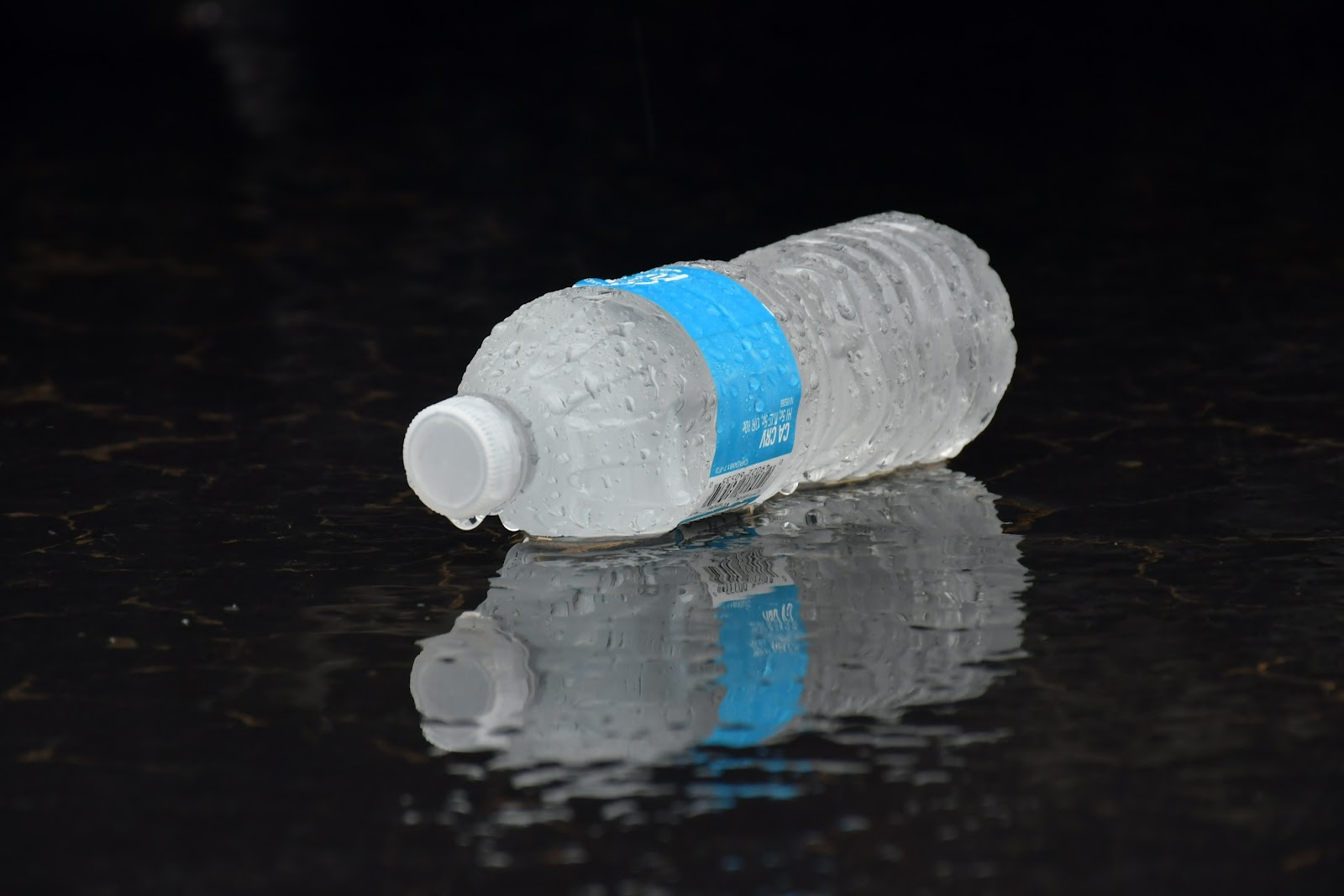 A bottle of water sits on the ground.