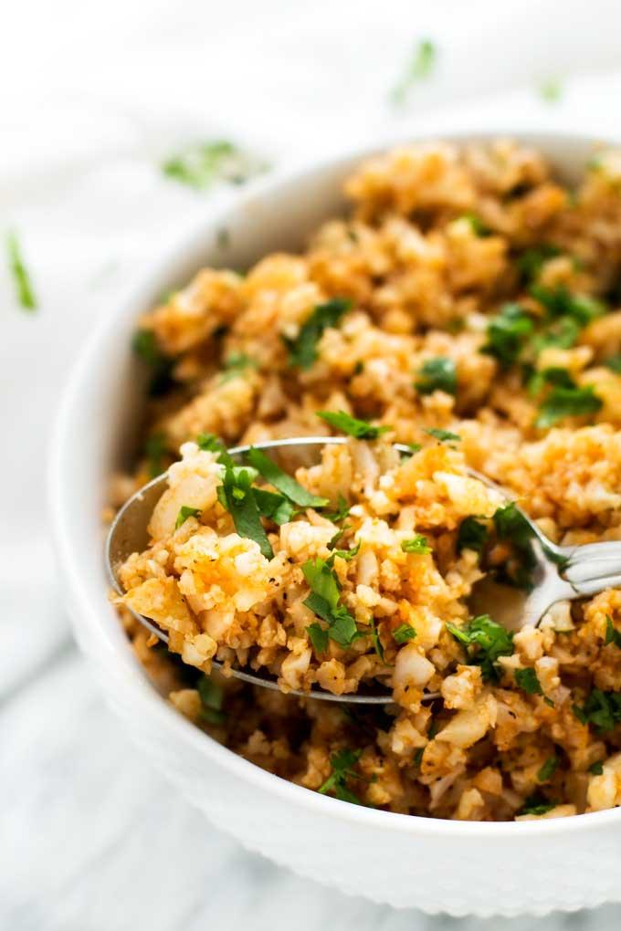 Close up photo of a bowl of Keto Spanish Rice with a spoon in it.