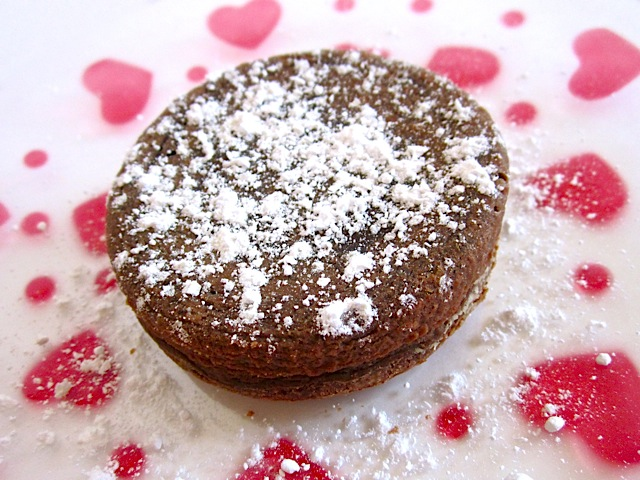 baked lava cake on heart plate and topped with powdered sugar