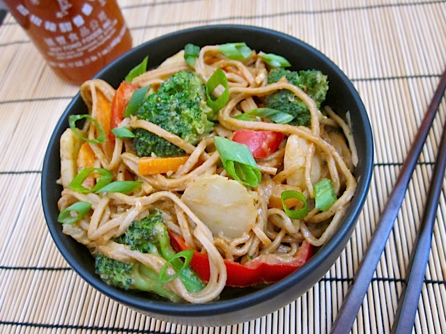 peanut soba stir fry in black bowl with chopsticks and a bottle of Sriracha on the side