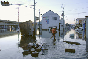 A person walks on a flooded street after a tsunami hit Iwaki, Fukushima Prefecture, northeastern Japan on March 11.