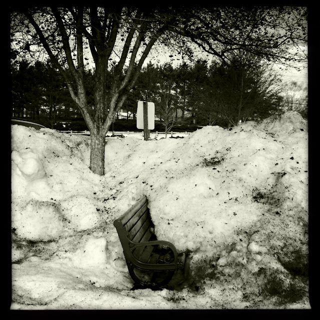 Bench half covered in dirty snow