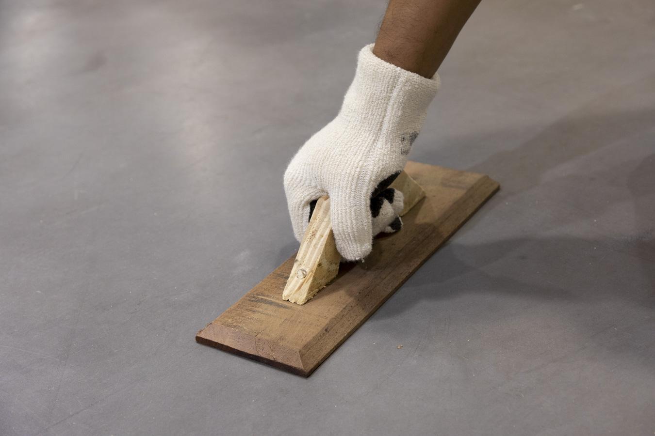 Una mano manejando una herramienta que distribuye un adhesivo para porcelanatos.