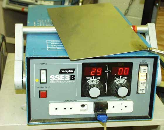 Photograph of an electrosurgical generator with grounding pad.