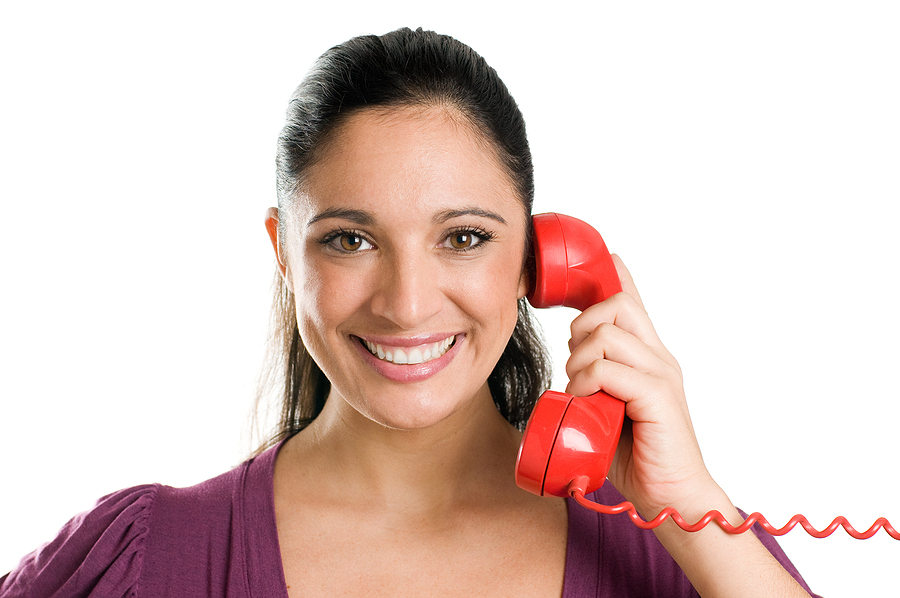 Young smiling woman on a bright red landline phone.
