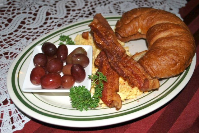 This is a photo of bacons and eggs and a croissant at Mishi's Strudel Cafe.
