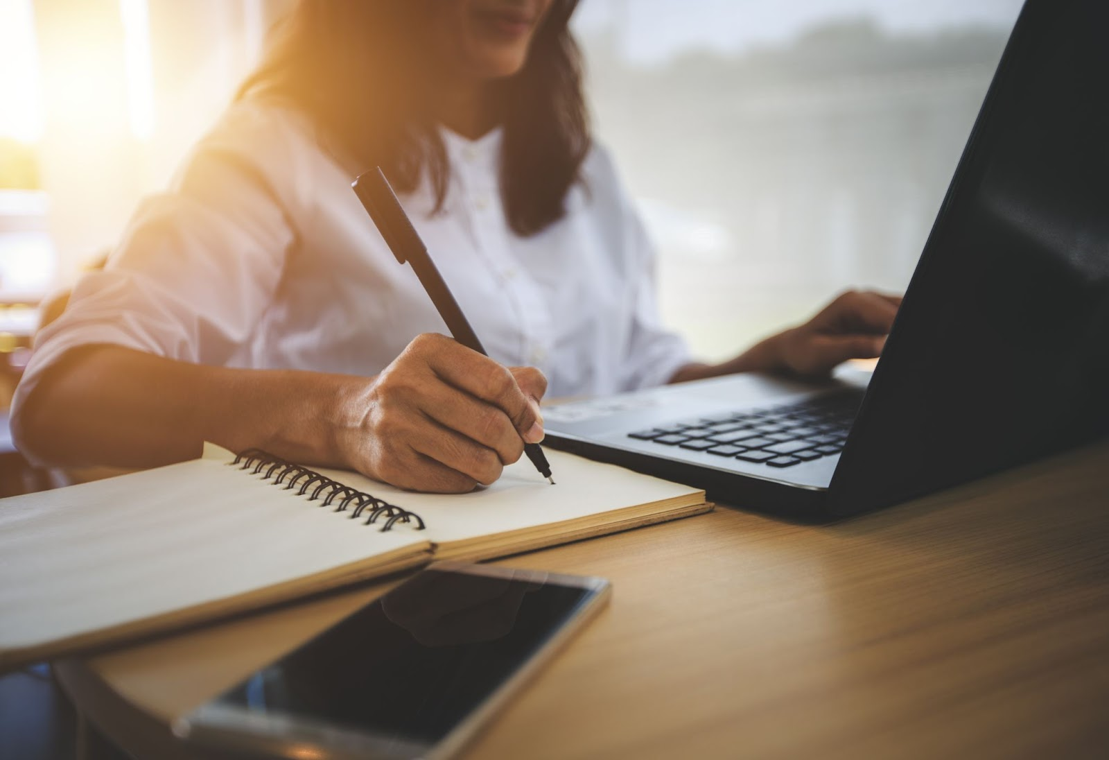 A woman uses a laptop and writes in a notebook