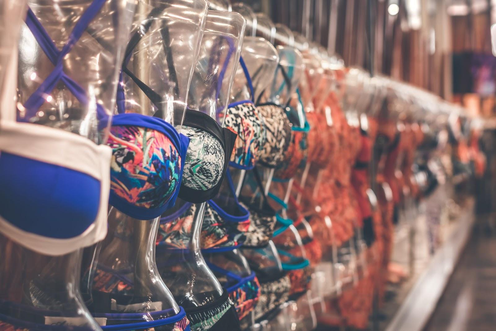 Tipos de biquínis expostos em cabides e modelos de plástico.