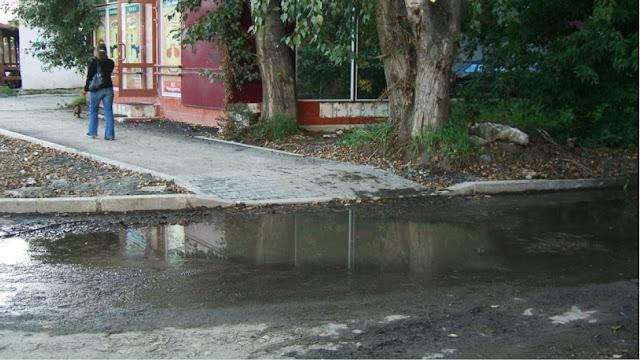 Лужа на выезде из двора дома №81 по ул. Посадской, пересечение с тротуаром