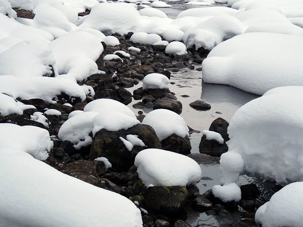 snow pillows on rocks in the river