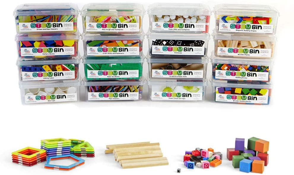This is a photo of STEM kits for elementary students all packaged in clearly labeled STEM bins.  The contents of the kits are spread out in front of the bins, including brick building blocks, magnetic tangrams, base ten blocks and cubes.