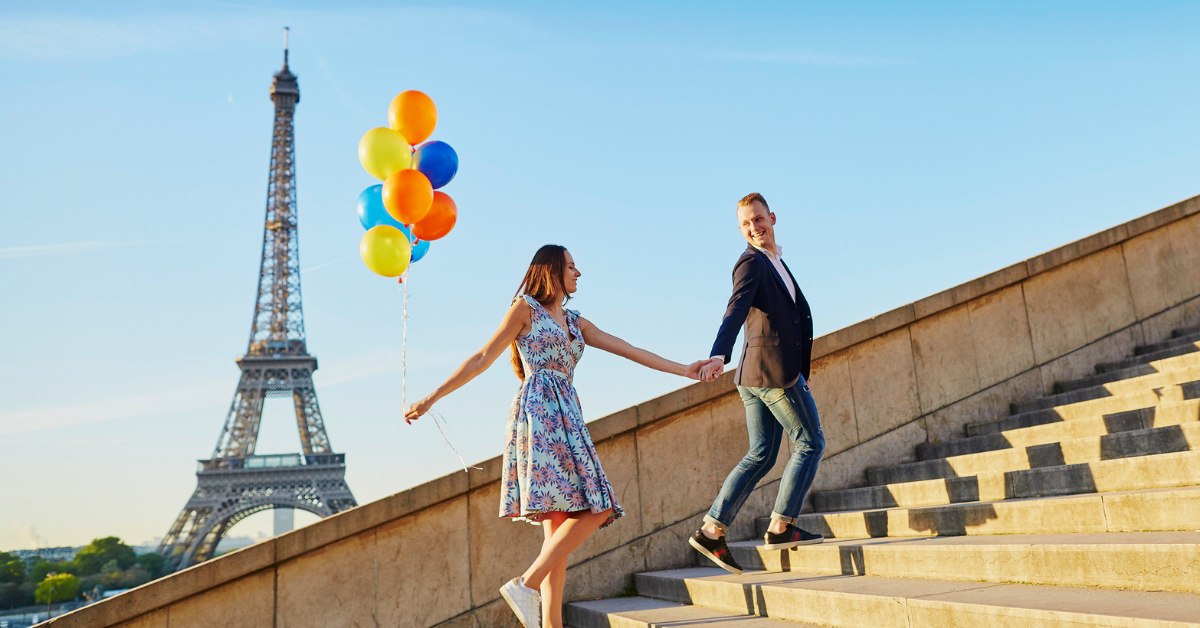 A couple climbing some stairs in front of the Eiffel Tower
