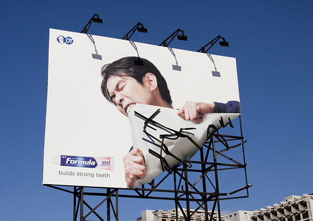 Man biting the corner of a billboard in advertisement for toothpaste.