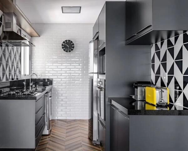 Cozinha com paredes com azulejos geométricos preto e branco e parede com azulejo do metrô branco, armários cinza em harmonia com eletrodomésticos cinzas.