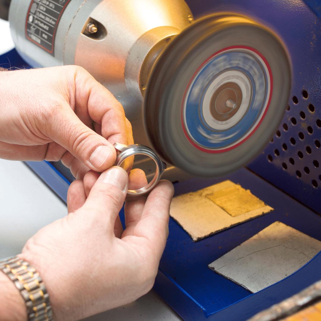 Photo of a man polishing a watch with the help of a watch polishing machine