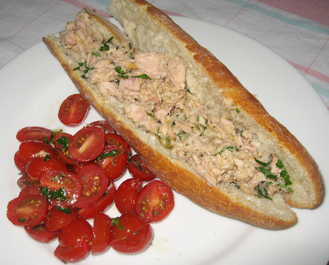 an Italian tuna sandwich with tomato salad