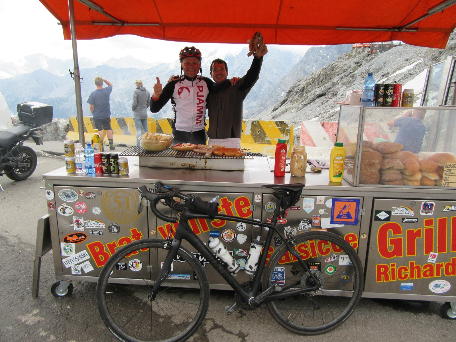 Umbrail Pass bike climb - bratwurst and food cart at passo dello stelvio with cyclist, bike and cook