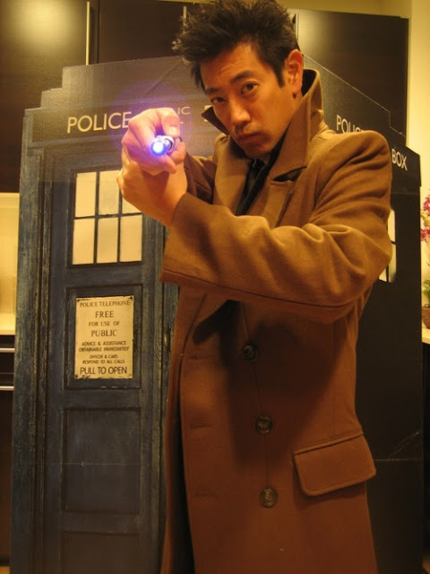 a picture of Grant Imahara wearing a tenth doctor-esque trenchcoat, holding a sonic screwdriver, and standing in front of a TARDIS cutout