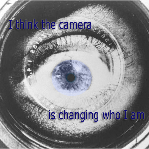 Secret 20 - Image: an eye reflected in a camera lens. Text: I think the camera is changing who I am. Font: sans-serif.