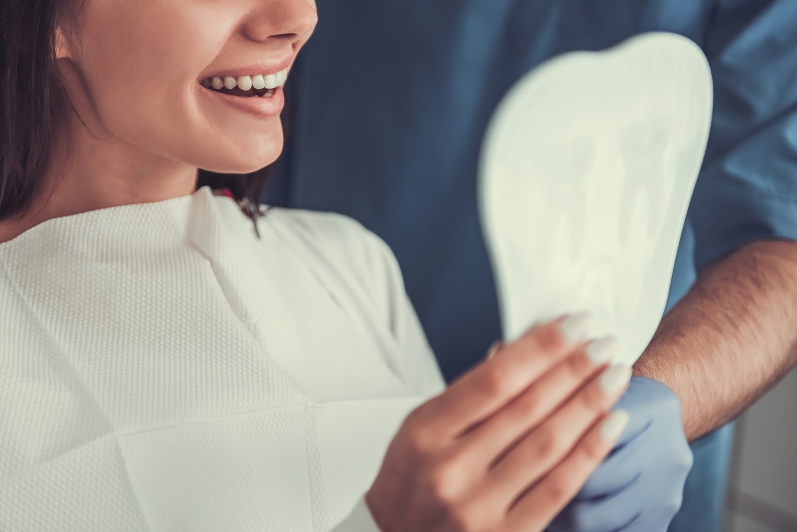 patient admires their smile after dental treatment