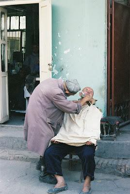 青空床屋でひげを剃られる老人