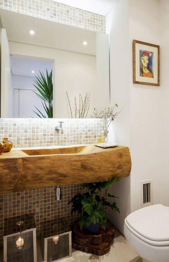 Lavabo em estilo rústico com pia de madeira que reproduz tronco de árvore, pastilhas em tons neutros, plantas decorativos e acessórios rústicos.