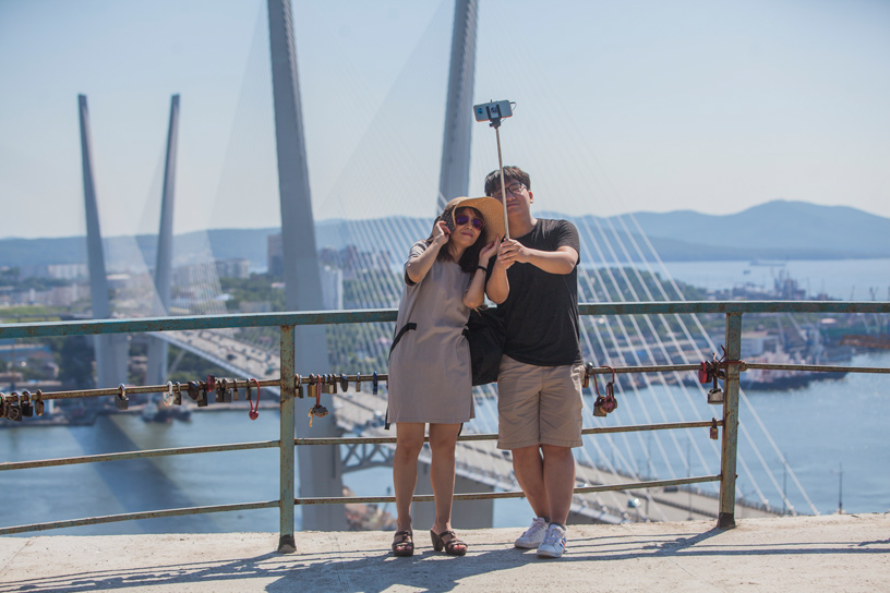 Free Port of Vladivostok. Tourists taking photo in front of the Golden Bridge