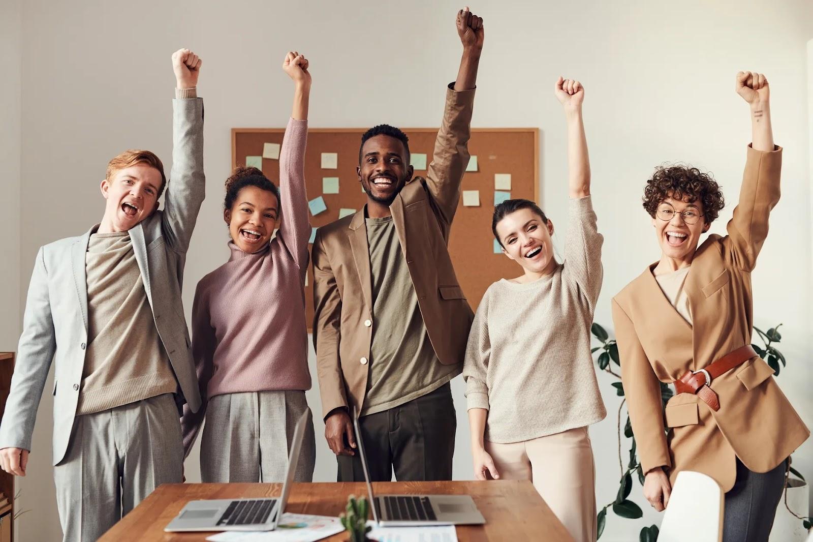 Pessoas levantando a mão esquerda em sinal de comemoração no local de trabalho