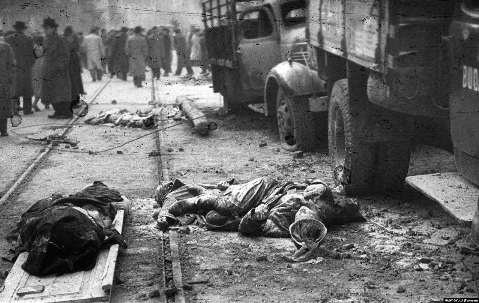Покрытые пылью тела в форме в Будапеште в 1956 году. В ходе восстания советские войска были на четыре дня выведены из Будапешта. Восставшие открыли двери тюрем, чтобы выпустить политзаключенных, а также убили некоторых наиболее ненавистных сотрудников госбезопасности