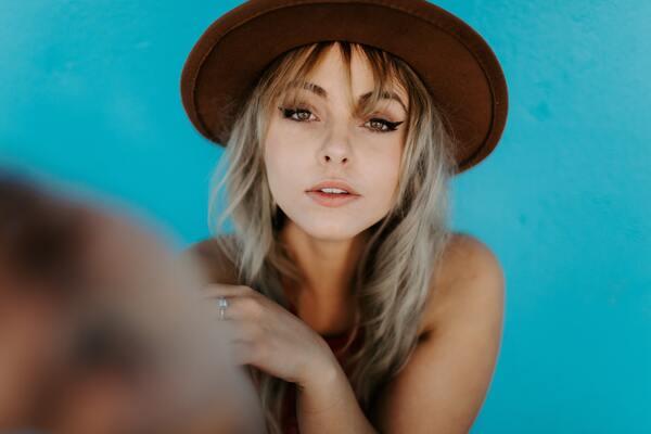 foto de uma mulher loira em fundo azul usando chapéu
