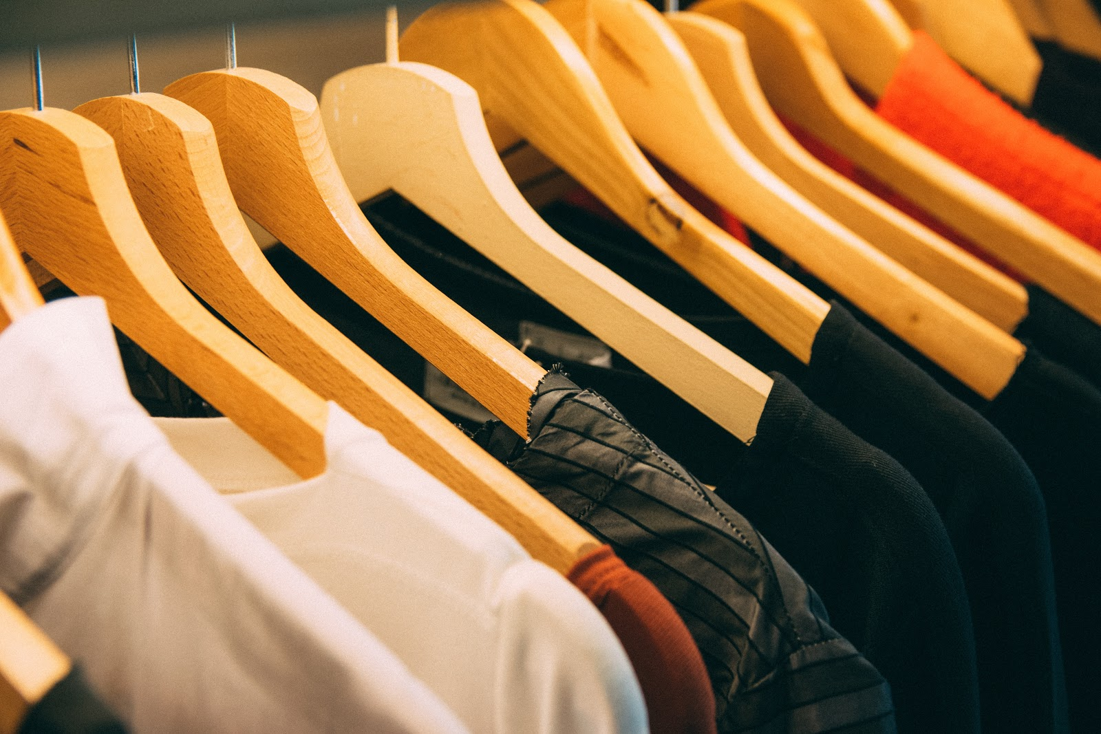 Different shades of clothes on wooden hangers meant to encourage you to reduce waste by not buying new clothes