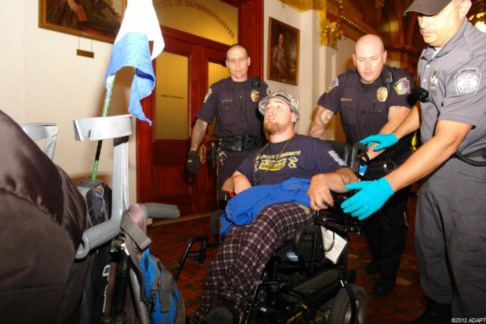 Man in wheelchair being dragged out of a government building by state police.
