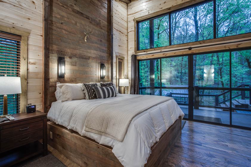 wood bedroom with large doors and windows